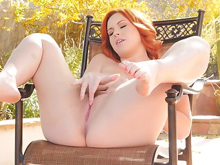 Bosomy redhead spreads her pussy and plays with tits outdoors